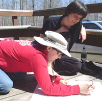 Photo of Amy and Melina outside, working on a project