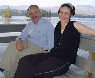 Photo of Mark and Melina outsdie, sitting on a bench with a view of the lake behind them.