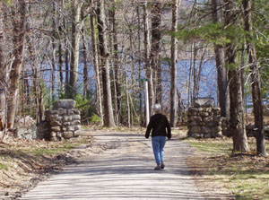 Photo of Cathy walking outside, going down the driveway toward the trees and lake.