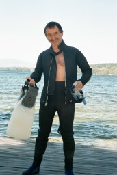 Photo of Chris Rowe in scuba gear standing in front of the lake.