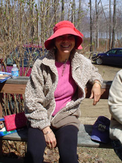 Photo of Claire smiling, sitting on a bench outside