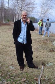 Photo of Dan standing outside in front of the water, talking on his cell phone