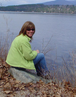 Photo of Kelly sitting on a rock in front of the lake