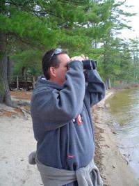 Photo of Ken looking through binoculars across the lake