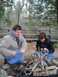 Photo of Ken and Jane kneeling by a pile of wood which will soon be a campfire.