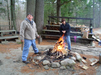 Photo of Ken and Jane outsdie, standing by the campfire.