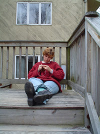 Photo of Marcy outside sitting at the top of the steps, deeply engrossed in what she's doing