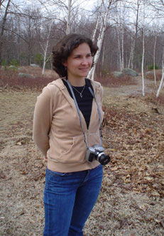 Photo of Mariana standing outside with a camera around her neck