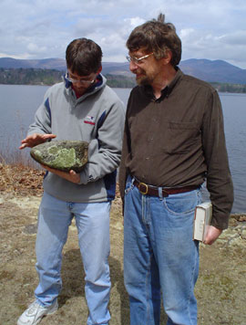 Photo of Mark and Steve outside in front of the Lake, looking at a large rock that Mark is holding