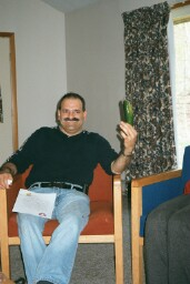 Photo of Terry inside sitting in a chair and holding up a cuc.