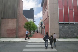 What the Amesbury Street Alley would look like after, depicting a new sidewalk, clean painted or restored building sides and trees and plants along the walkway, giving it a clean, inviting look to it.