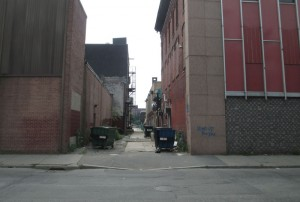 What the Amesbury Street Alley looks like before with; old and broken sidewalk, garbage dumpsters, weeds, and dirty or oddly painted building sides.